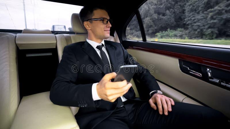 Успешный усмехаясь финансовый эксперт имея езду в аэропорт в роскошном автомобиле, отключение стоковые изображения