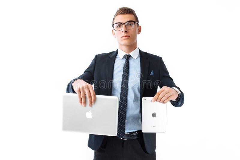 Успешный человек в стеклах и костюме держит планшет в одном Хане стоковое изображение rf