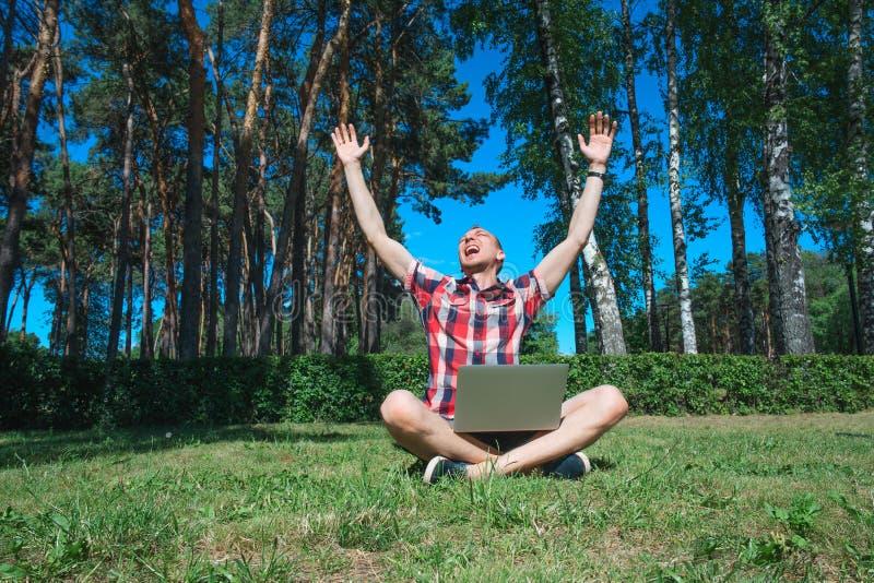 Успешный человек при outoor компьтер-книжки работая сидя на траве стоковое изображение