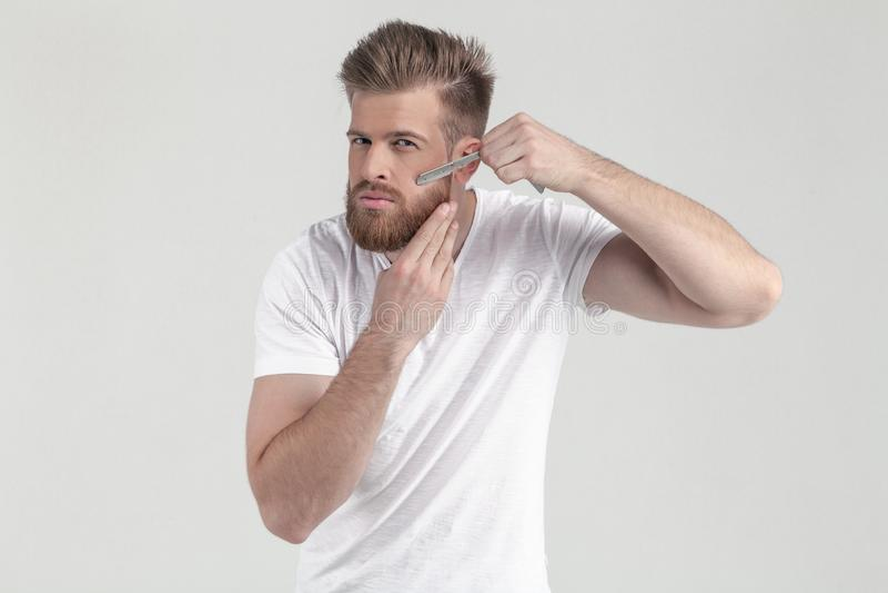 Успешный человек с сочной бородой имбиря уколите вверх консервные банки на бороде смотря камеру одетый в случайных одеждах стойте стоковое изображение rf