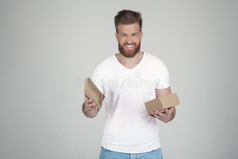 Успешный человек с сочной бородой имбиря с улыбкой на его стороне смотря в камеру с открытым подарком одетый в случайном стоковое изображение