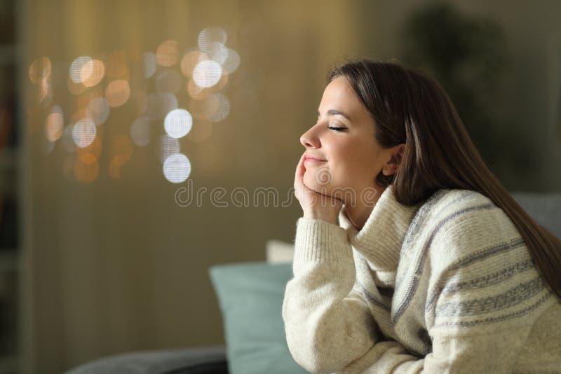 Успокоенная женщина медитирует дома ночью зимой стоковая фотография rf