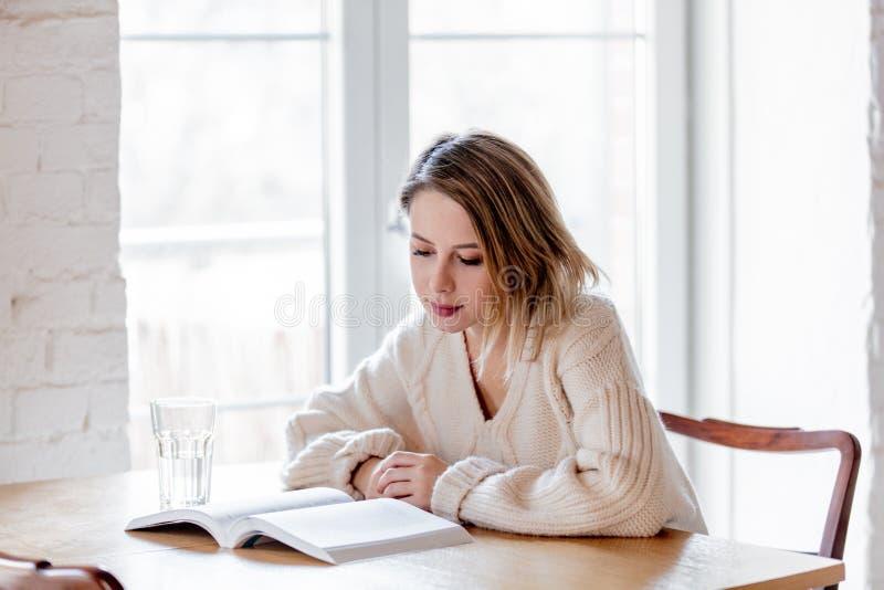 Уставшая девушка в белом свитере с книгой на кухне стоковая фотография