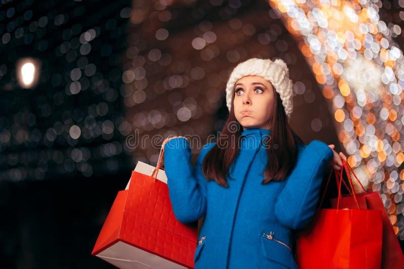Уставшая девушка держа хозяйственные сумки на светах рождества Décor стоковое фото rf