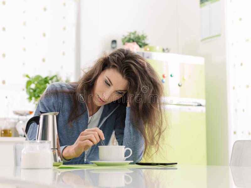 Уставшая женщина имея завтрак дома стоковое изображение rf