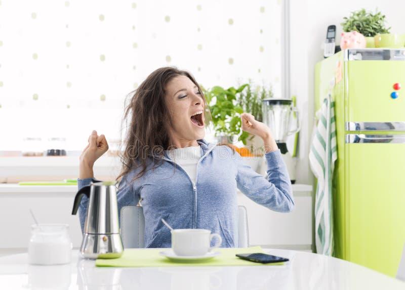Уставшая женщина имея завтрак дома стоковая фотография rf
