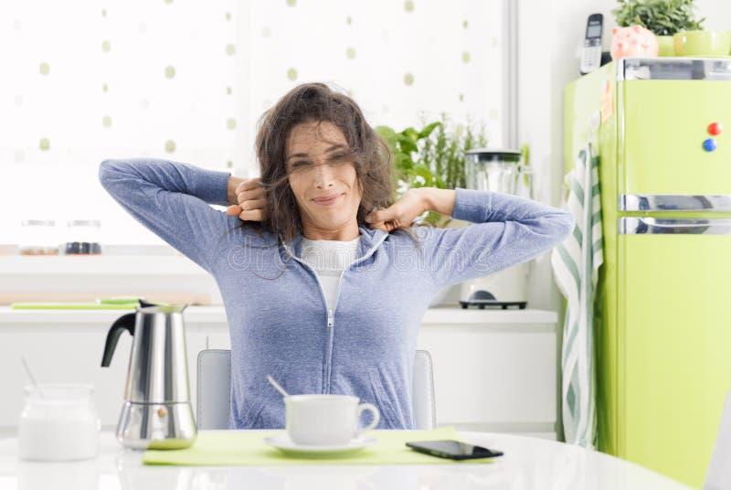 Уставшая женщина имея завтрак дома стоковые изображения rf