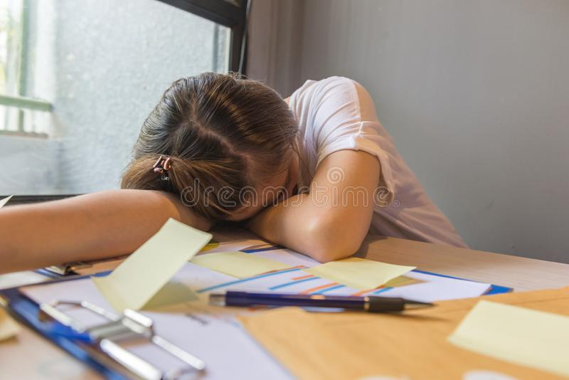 Уставшая женщина офиса спать на рабочем месте стоковые фотографии rf