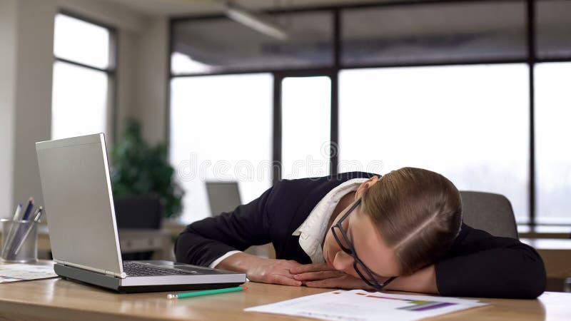 Уставшая женщина спать в офисе, отдыхающ от монотонных задач и перегрузок стоковые фотографии rf