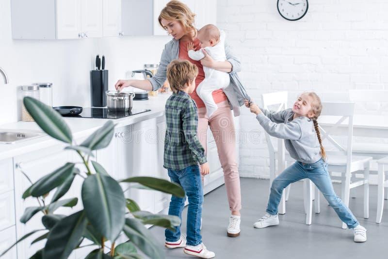 уставшая мать держа младенческого ребенка и варя пока капризная игра детей иллюстрация вектора