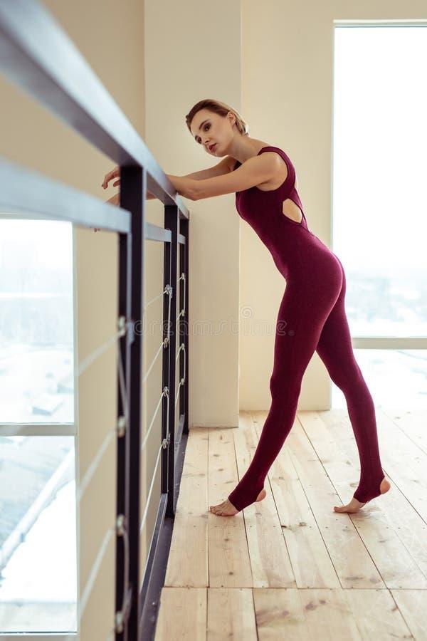 Уставшая симпатичная женщина полагаясь на перилах металла после выматывать тренировку стоковое изображение rf