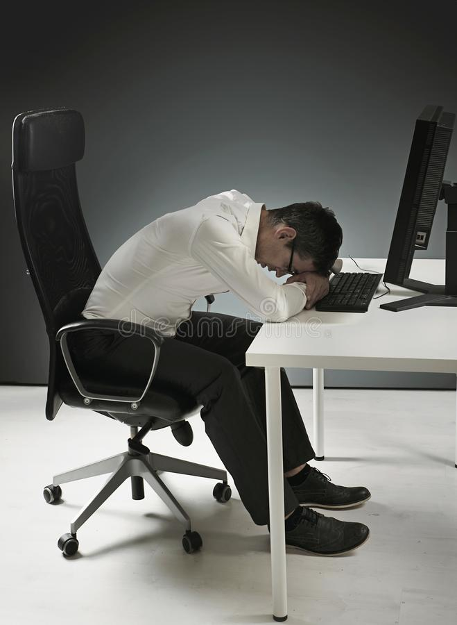 Уставший бизнесмен имея ворсину на столе стоковое фото