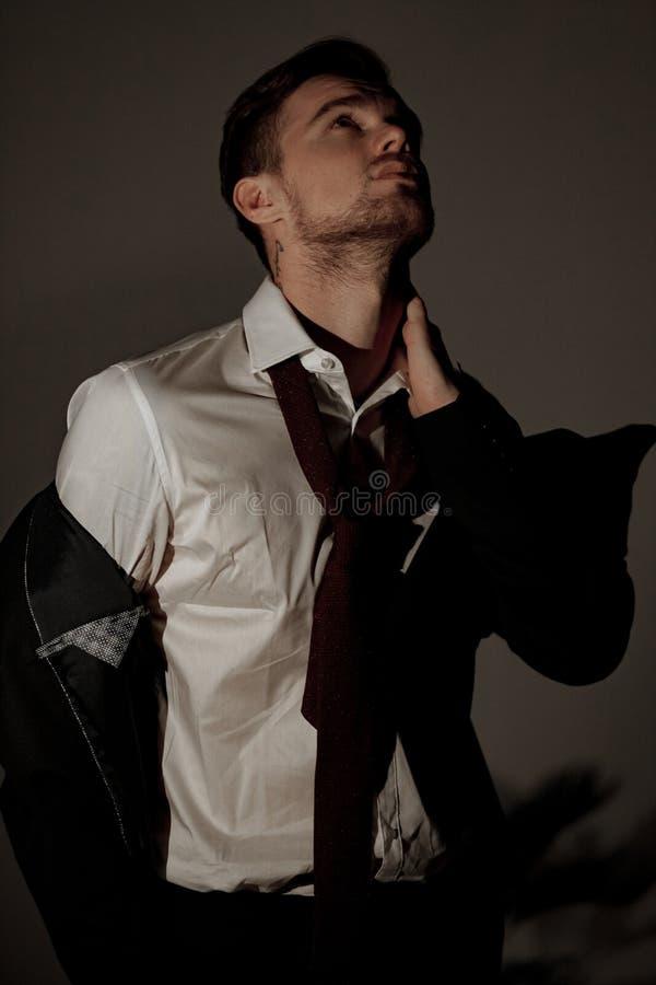 Уставший бизнесмен стоит в рубашке с принимать куртку и стоковое фото