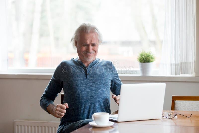 Уставший достигший возраста человек протягивая в страдании стула от боли в спине стоковые изображения