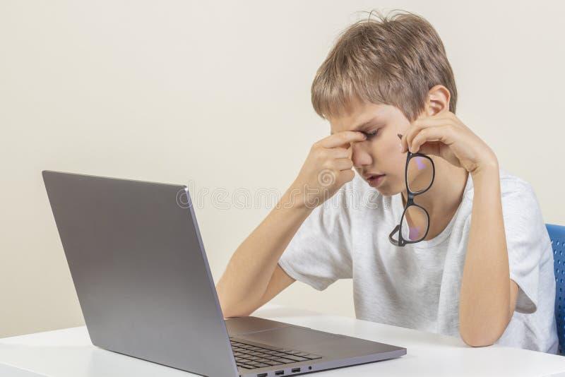 Уставший мальчик с ноутбуком сидя на таблице стоковая фотография rf