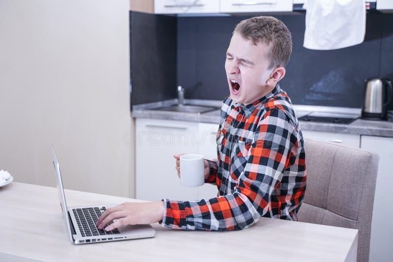 Уставший молодой человек в рубашке шотландки сидя на таблице перед ноутбуком самостоятельно зевки подростка в процессе образовани стоковые фотографии rf
