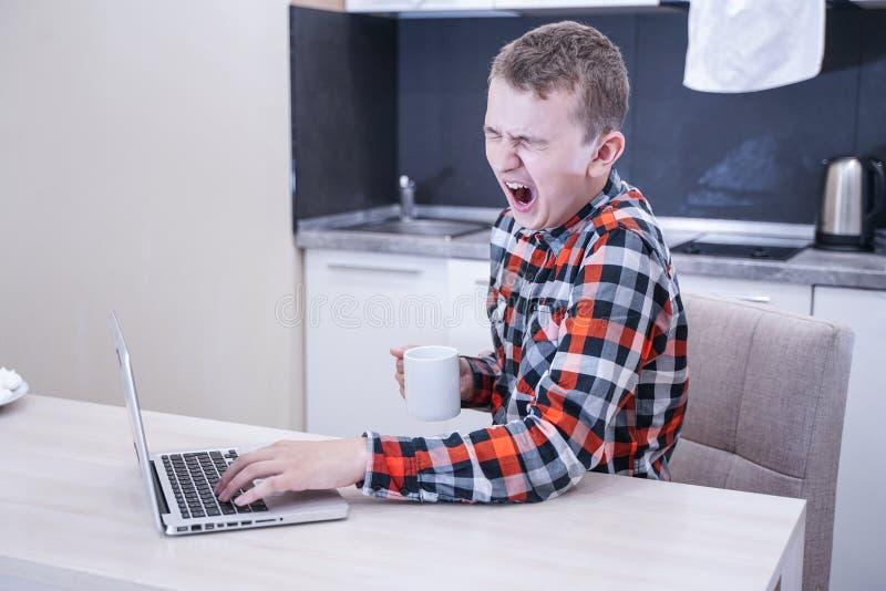 Уставший молодой человек в рубашке шотландки сидя на таблице перед ноутбуком самостоятельно зевки подростка в процессе образовани стоковые изображения rf