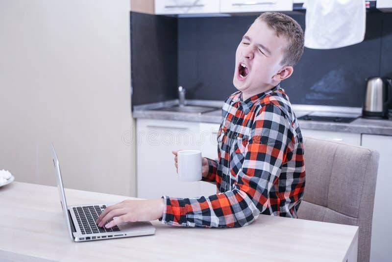 Уставший молодой человек в рубашке шотландки сидя на таблице перед ноутбуком самостоятельно зевки подростка в процессе образовани стоковое фото
