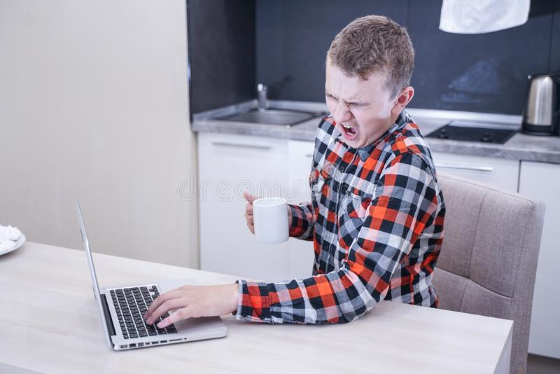Уставший молодой человек в рубашке шотландки сидя на таблице перед ноутбуком самостоятельно зевки подростка в процессе образовани стоковое изображение rf
