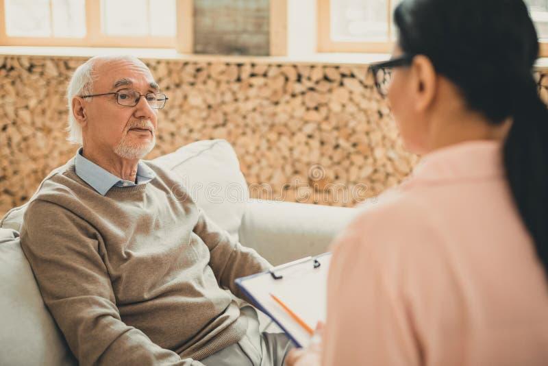 Уставший старик отдыхая на кресле и смотря на его волонтере стоковое фото rf