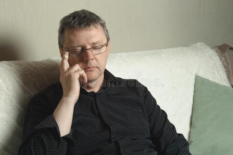 Уставший человек со стеклами сидит на софе стоковые изображения rf