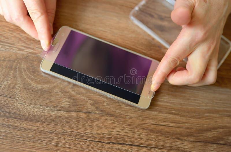 Устанавливать защитное стекло на smartphone стоковое изображение rf