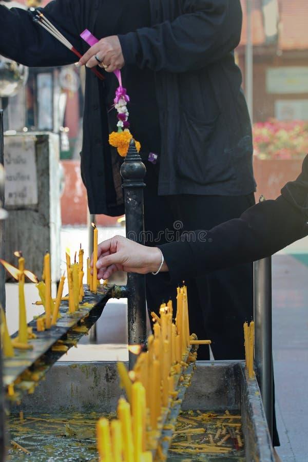 Устанавливать освещенную свечу на алтаре Будды стоковые фотографии rf