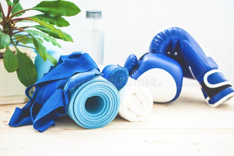 Установите для спорт, циновки йоги, полотенца, перчаток бокса и бутылки воды на светлой предпосылке Концепция здорового образа жи стоковое фото rf