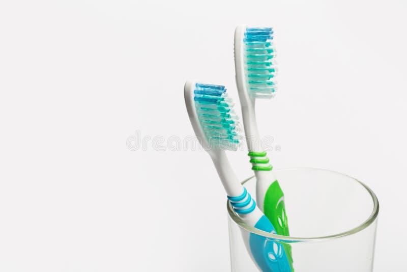 Установите зубных щеток в стекле на белой предпосылке стоковое изображение