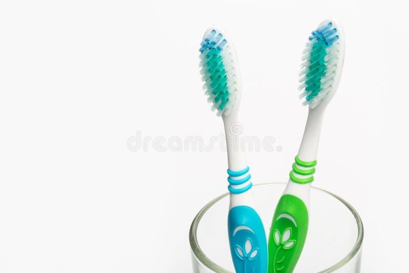 Установите зубных щеток в стекле на белой предпосылке стоковая фотография