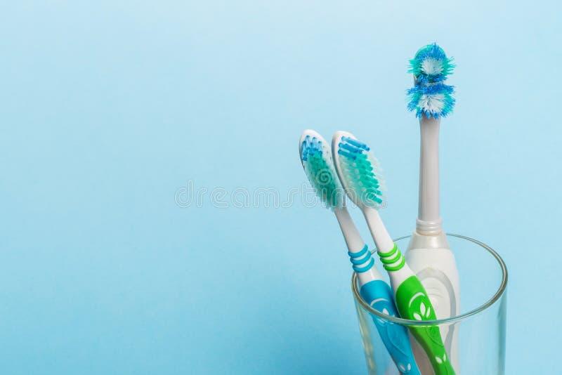Установите зубных щеток в стекле на голубой предпосылке стоковое изображение