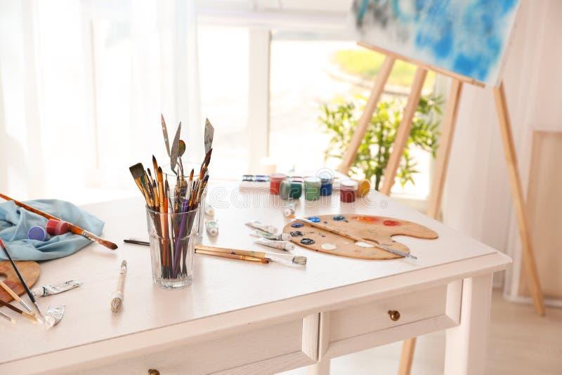 Установите инструментов с красками на таблице в мастерской художника стоковое изображение