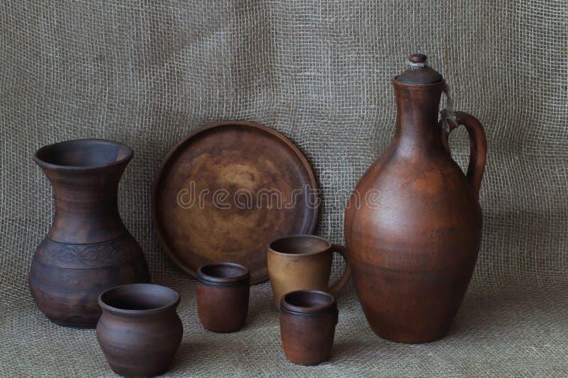Установите керамической посуды: кувшин для вина, круглого блюда, стекел, вазы, бака, кружки на ткани домодельного джута простой К стоковое изображение rf