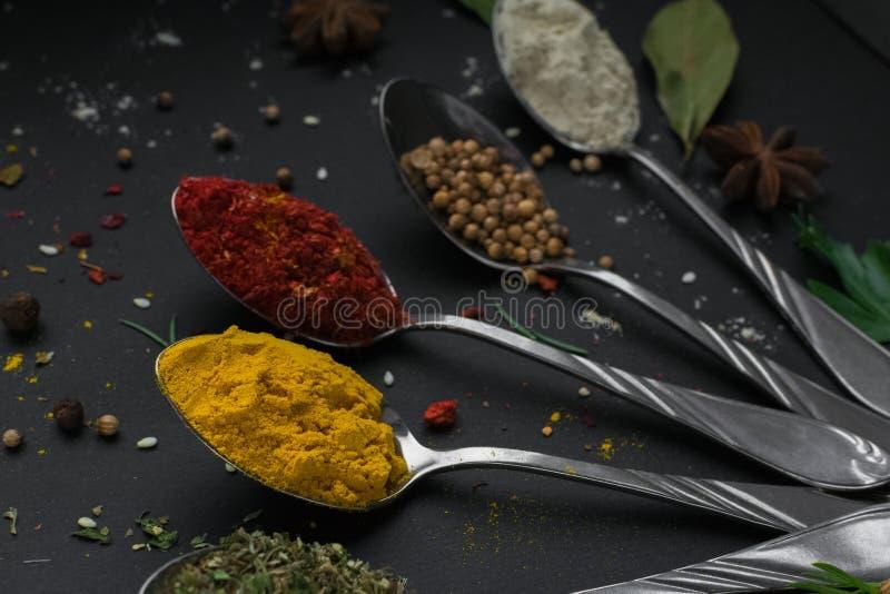 Установите различных специй и трав на черной предпосылке шифера Перец, turmelic, имбирь, шафран, базилик, розмариновое масло, зяб стоковая фотография rf