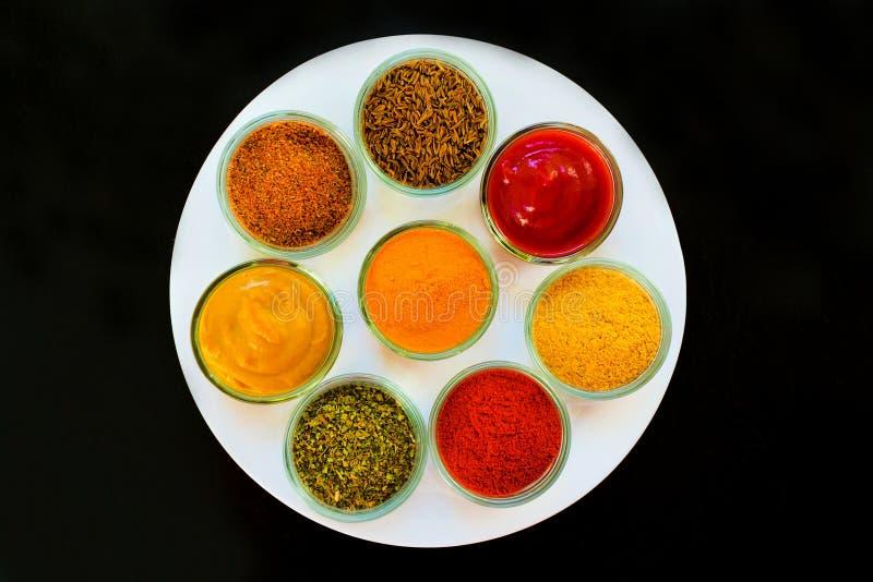 Установите специй и трав на белой плите Индийский перец кухни, соль, паприка, карри, мустард, мускат, турмерин : стоковые фотографии rf