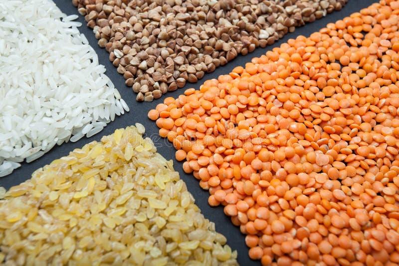 Установите хлопьев на черной предпосылке: чечевицы, рис, гречиха и булгур стоковая фотография rf