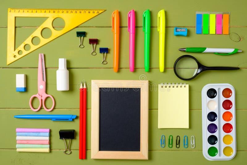 Установите школьных принадлежностей на предпосылке деревянного стола, творческом плане сделанном из канцелярских принадлежностей  стоковое изображение