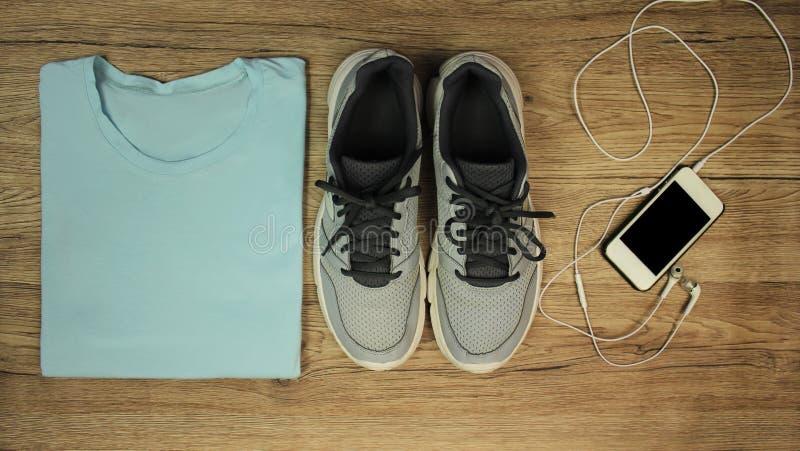 Download Установите для спорт: ботинки, футболка, мобильный телефон с концом-вверх на деревянной предпосылке, взгляд сверху наушников Стоковое Фото - изображение насчитывающей backhoe, деревянно: 81801550