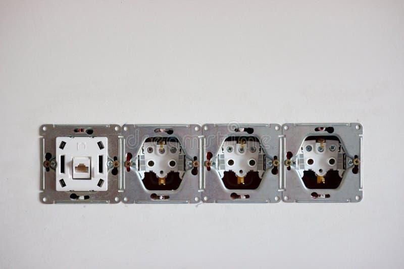 Установка гнезд и переключателей, соединителя 220 вольт для интернета грубый финиш в ремонте электрическая работа в стоковая фотография