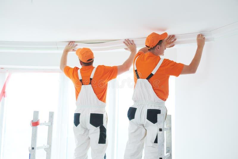 Установка декоративной прессформы потолка домашний ремонт и украшение стоковое изображение