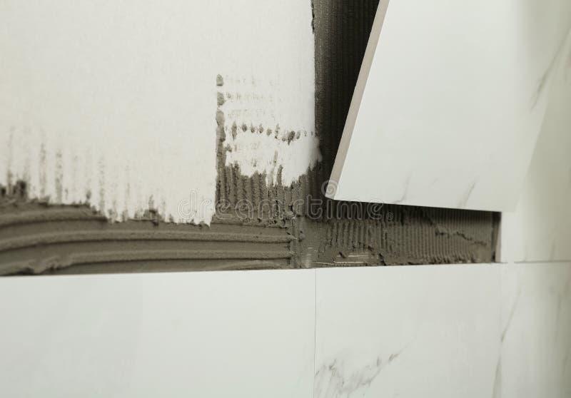 Установка керамической плитки на стену, крупный план стоковые изображения