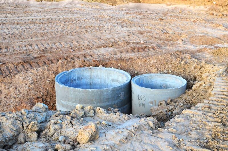 Установка конкретных колодцев сточной трубы в земле на строительной площадке стоковые фото
