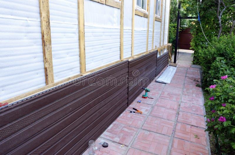 Установка коричневого пластичного siding на фасаде стоковые изображения