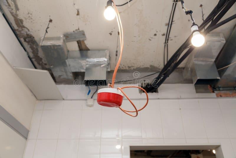 Установка крупного плана и ремонт электрического кабеля, индикатора дыма, аварийной системы пожарной сигнализации перед установко стоковые фотографии rf