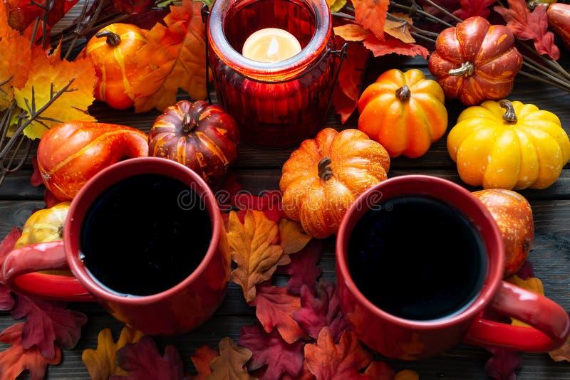 Установка осени при малые тыквы и красный держатель для свечи испуская свет на 2 чашках кофе утра стоковое изображение rf