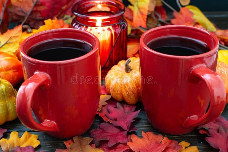 Установка осени при малые тыквы и красный держатель для свечи испуская свет на 2 чашках кофе утра стоковая фотография