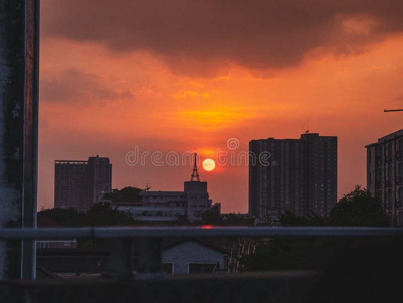 Установка солнца в городе над зданиями во время времени захода солнца стоковая фотография rf