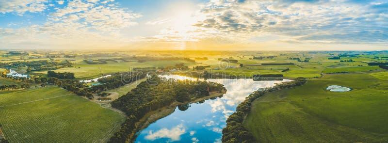 Установка Солнца над сценарными австралийскими злаковиками и выгонами сельской местности с рекой проходя до конца стоковое изображение