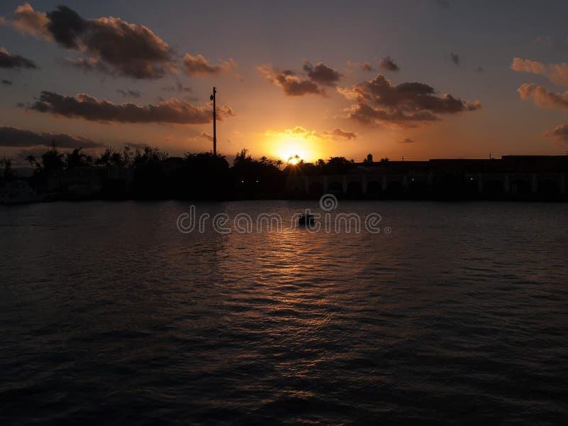 Установка Солнця за гаванью Сан-Хуана, Пуэрто-Рико, под темнотой заволокла небо стоковое фото