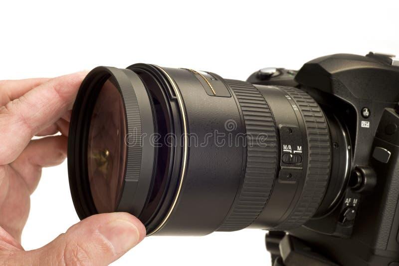 Установка фильтра на объектив фотоаппарата стоковая фотография